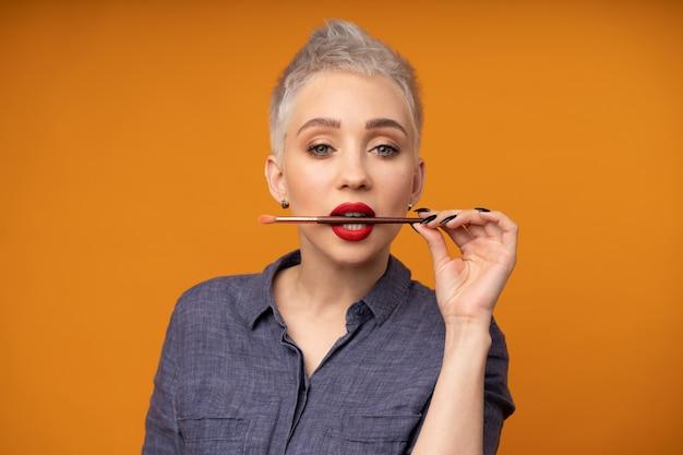 Retrato mulher com cabelo curto com pincel de maquiagem na mão