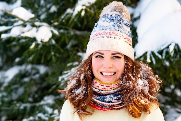 Retrato, mulher feliz em um fundo de neve, neve cai sobre a garota, a fêmea sorri no inverno em um lenço e um chapéu, ao ar livre do lado de fora.