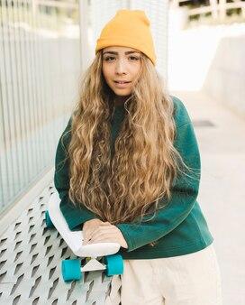 Retrato mulher jovem e bonita com skate