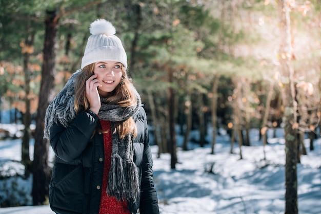 Retrato mulher jovem e bonita no inverno na neve usando telefone celular