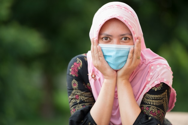 Retrato mulher muçulmana usando máscara, olhar para a câmera com prazer
