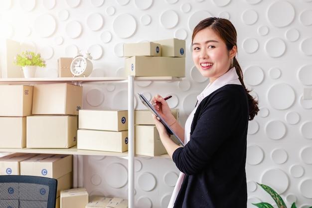 Retrato, mulheres jovens asiáticas, ficar, sorrizo, em, escritório lar