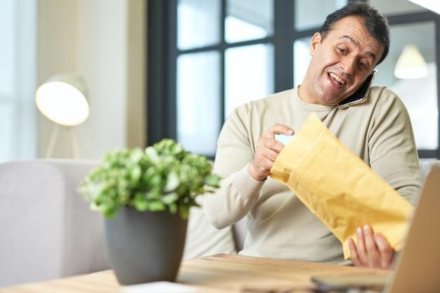Retrato multitarefa de homem de negócios hispânico de meia-idade falando ao telefone enquanto trabalhava