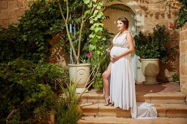 Retrato natural ao ar livre da linda mulher grávida em vestido branco