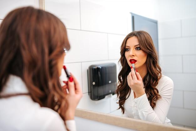 Retrato no espelho de uma menina bonita, aplicar o batom vermelho nos lábios.