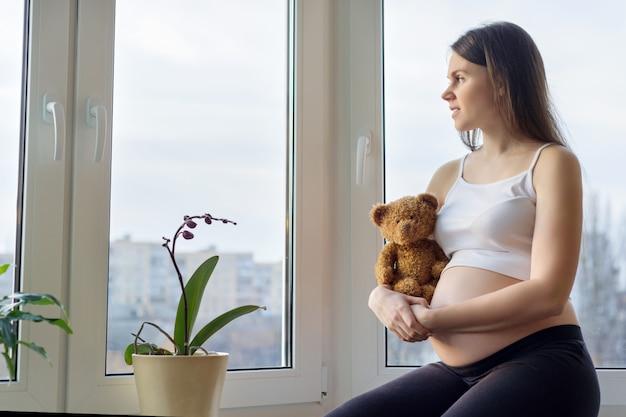 Retrato no perfil da bela jovem grávida
