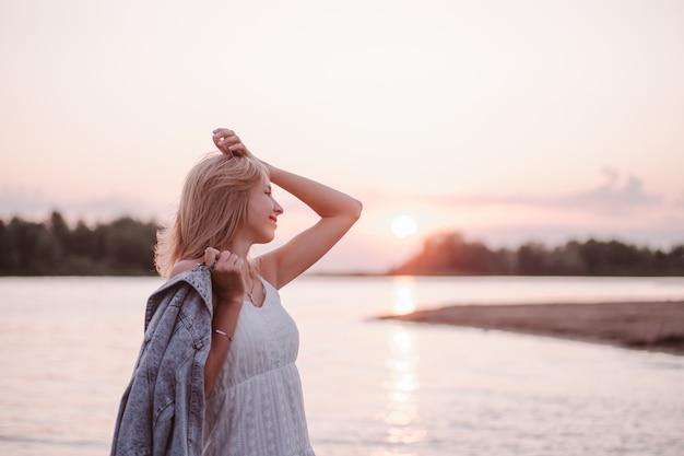 Retrato no perfil de uma jovem na praia, uma bela loira em um vestido branco de verão representa ...