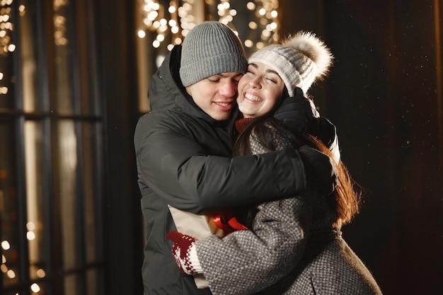 Retrato noturno ao ar livre de um jovem casal com caixa de presente