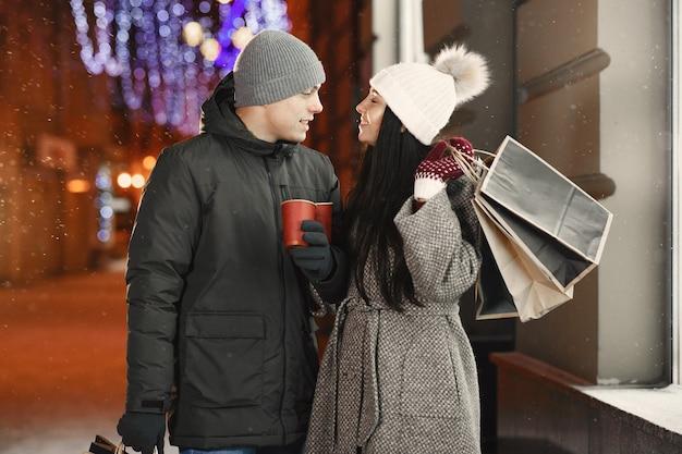 Retrato noturno ao ar livre de um jovem casal com sacolas de compras