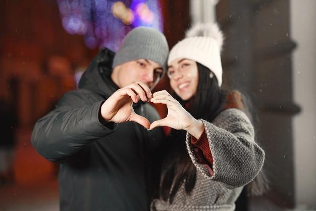 Retrato noturno ao ar livre de um jovem casal fazendo um coração com as mãos