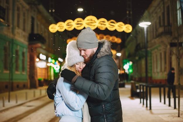 Retrato noturno ao ar livre de um jovem casal posando na rua