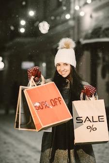 Retrato noturno ao ar livre de uma jovem com sacolas de compras