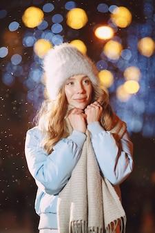Retrato noturno ao ar livre de uma jovem posando na rua