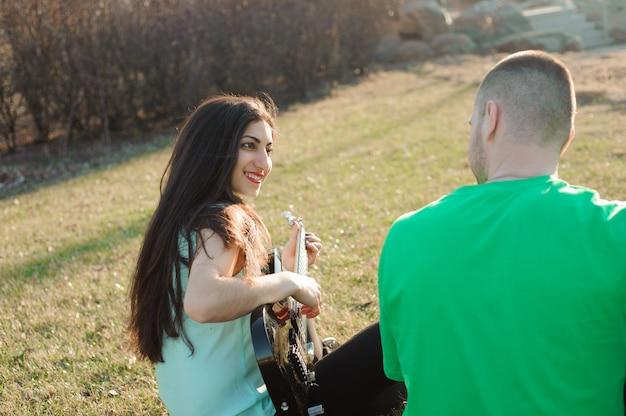 Retrato novo romântico dos pares que joga a guitarra sob o céu azul,