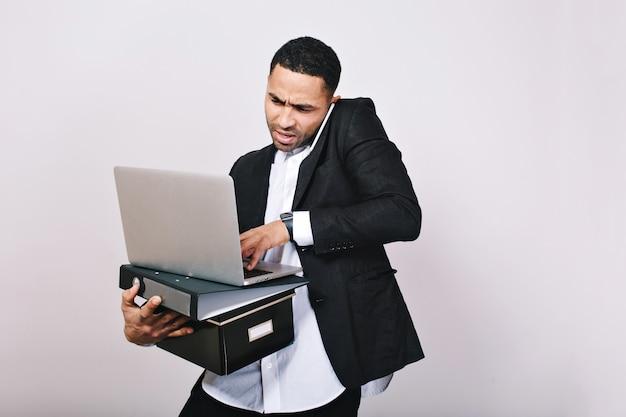 Retrato ocupado empresário atônito com pastas de escritório, laptop falando no telefone. trabalhador de escritório, carreira, mal-entendido, homem bonito e inteligente.