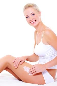 Retrato oh feliz alegre linda mulher aplicando creme hidratante corporal, sentada na cama