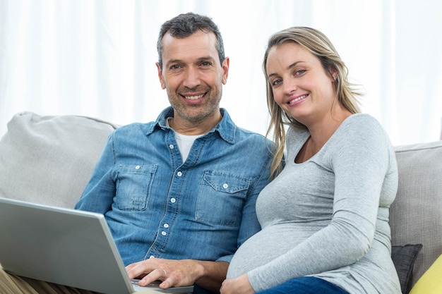 Retrato, par, sentando, junto, sofá, usando, laptop