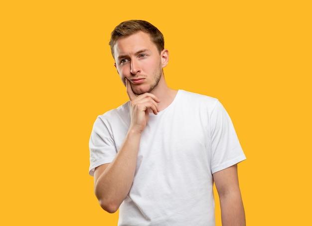 Retrato pensativo do homem. escolha difícil. cara pensativo, considerando a opção isolada em fundo laranja.