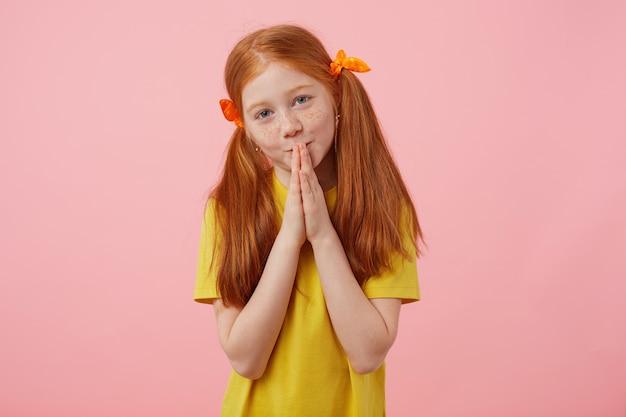 Retrato pequena menina ruiva sardas arrependida com duas caudas, olha para a câmera e as mãos em concha juntas, gesto de presa, usa uma camiseta amarela, fica sobre fundo rosa.