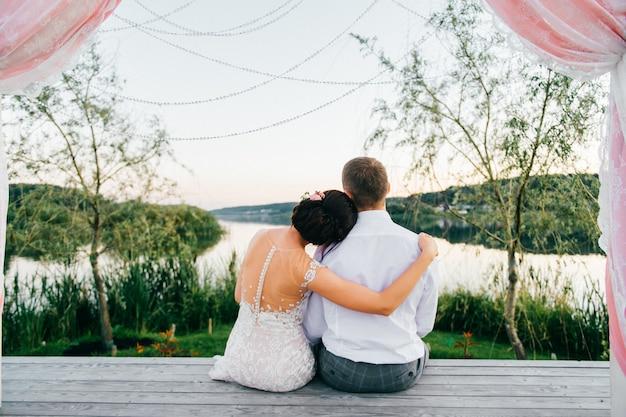 Retrato por trás do casal nupcial sentado no lugar de madeira e olhando para o lago.
