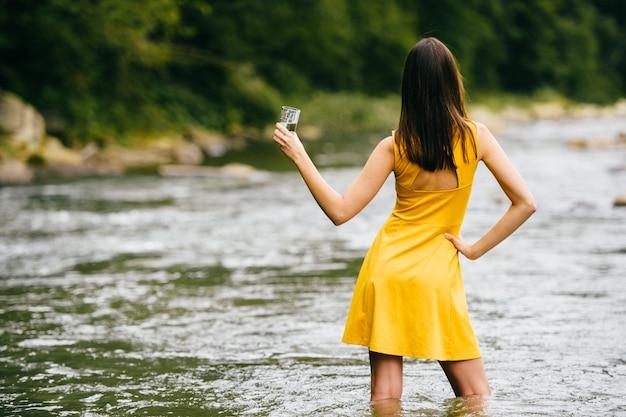 Retrato por trás do modelo moreno sexy vestido amarelo de pé no rio verão com um copo de água na mão.
