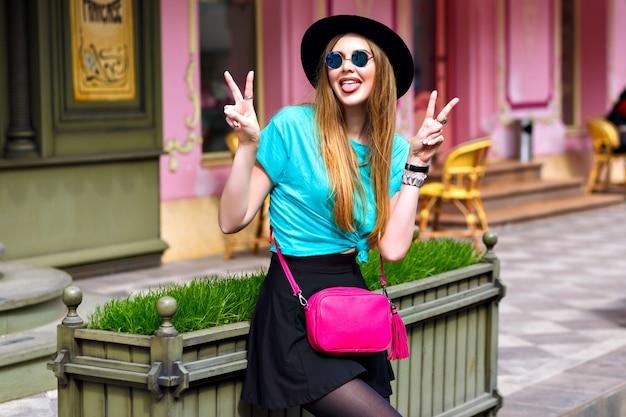 Retrato positivo de moda ao ar livre de menina elegante hipster, longos cabelos loiros, chapéu vintage, roupa de estilo de rua brilhante, posando perto de um lindo café francês, alegria, viagens, roupa.