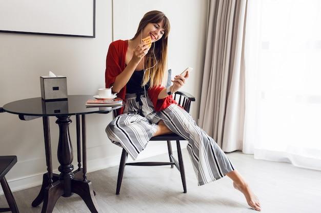 Retrato positivo de primavera de uma jovem sentada na sala de estar
