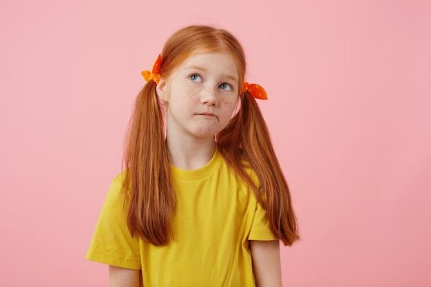 Retrato pouco pensativo sardas garota ruiva com duas caudas, desvia o olhar, toca as bochechas, usa uma camiseta amarela, fica sobre um fundo rosa com espaço de cópia.