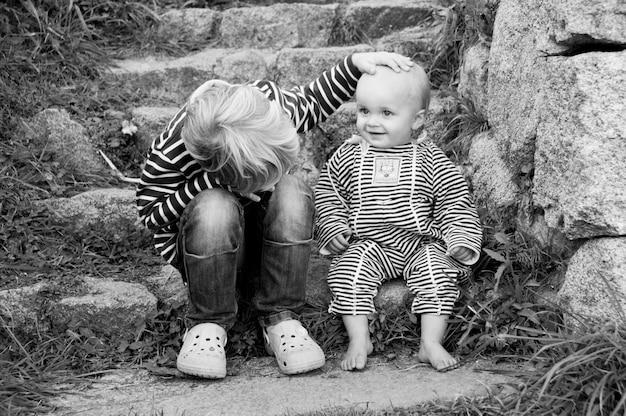 Retrato preto e branco de dois meninos no campo