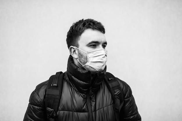 Retrato preto e branco de um homem com uma máscara de um vírus. proteção contra covid-19. quarentena na cidade.