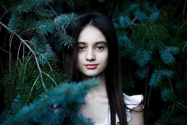 Retrato preto e branco de uma linda adolescente posando entre os galhos de pinheiro.