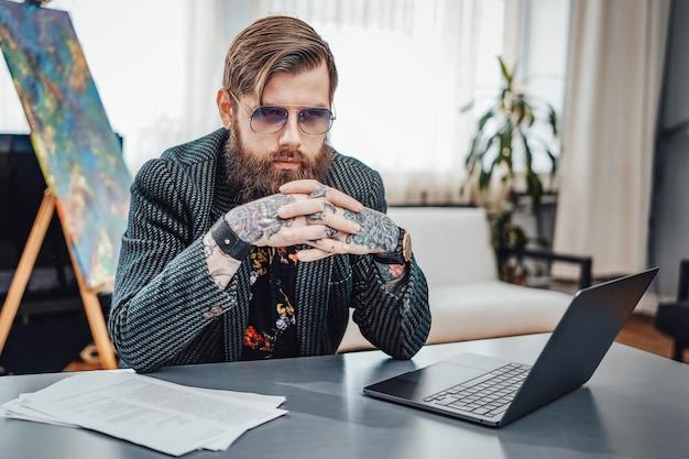 Retrato profissional de um freelancer estilizado com tatuagens, vestindo terno personalizado, ele se senta à mesa com um laptop.
