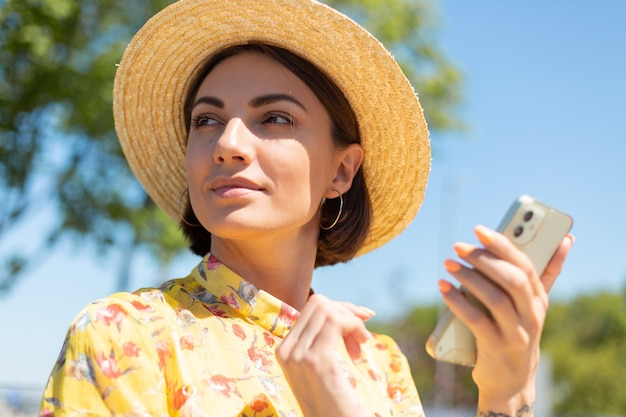 Retrato próximo ao ar livre de mulher com vestido amarelo de verão e chapéu em um dia ensolarado segura o telefone celular e olha para a esquerda