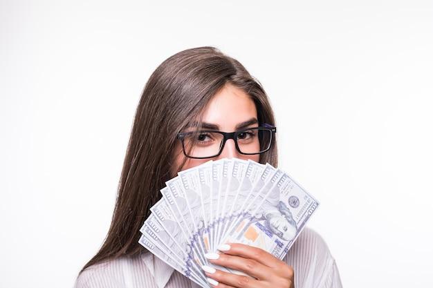 Retrato próximo de mulher de negócios com longos cabelos castanhos em roupas casuais segurando muitas notas de dólar