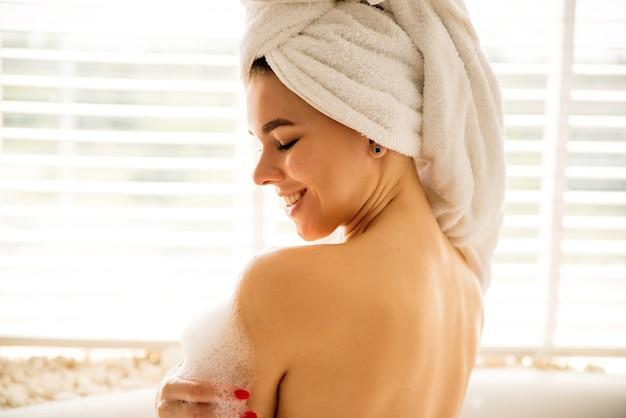 Retrato próximo de uma menina que se lava em uma banheira com espuma ela tem uma toalha branca na cabeça ela gosta de cuidar de si mesma