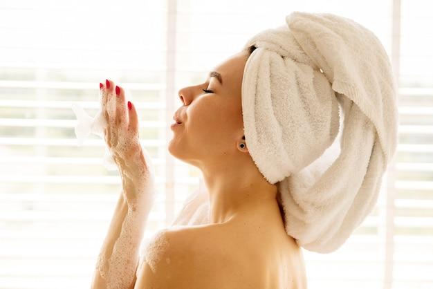 Retrato próximo de uma menina tomando banho de espuma ela tem uma toalha branca na cabeça ela sopra na espuma gosta de estar em um lugar com ela