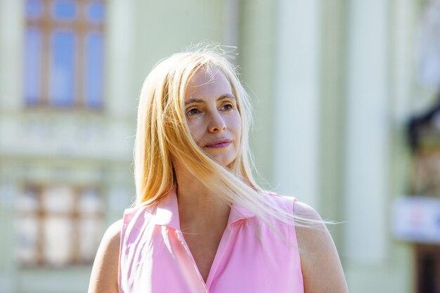 Retrato real mulher feliz loira meia idade natureza verão cabelos longos luz solar cinquenta mais 50 rua rosa