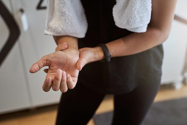 Retrato recortado da cabeça de uma esportista em roupas esportivas pretas examinando o pulso na mão enquanto passa um tempo no vestiário
