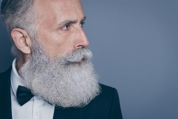 Retrato recortado da vista lateral do perfil em close-up dele ele bom conteúdo masculino atraente e bem cuidado homem de cabelos grisalhos olhando de lado isolado sobre o fundo cinza violeta roxo