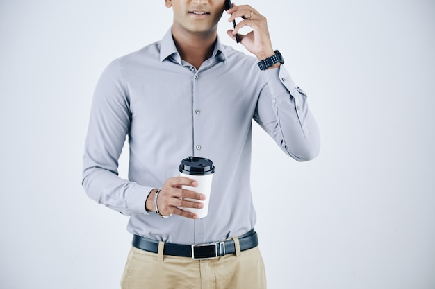 Retrato recortado de empresário confiante com uma xícara de café para viagem falando ao telefone com um colega