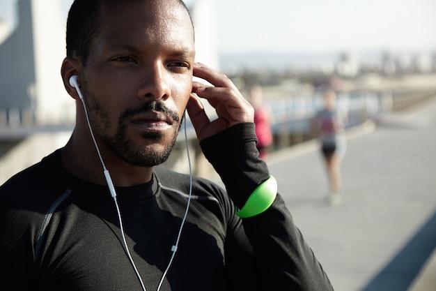 Retrato recortado de esportista preto sentado na calçada em pensamentos profundos, ouvindo audiolivro motivacional em seus fones de ouvido, tocando sua cabeça, parecendo confiante e concentrado durante o treino