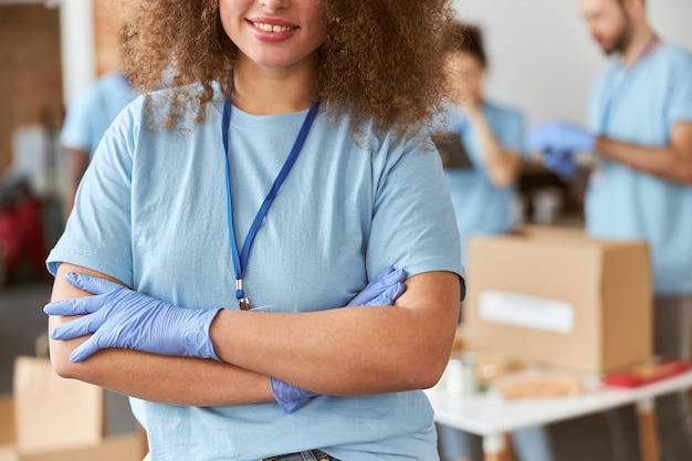 Retrato recortado de jovem voluntária em uniforme azul sorrindo para a câmera em pé