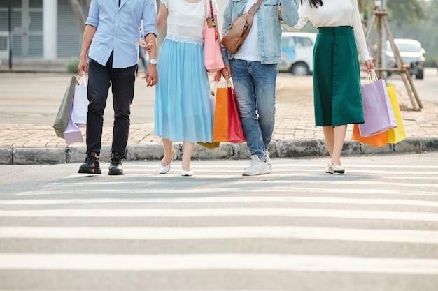 Retrato recortado de jovens com sacolas de compras andando na faixa de pedestres