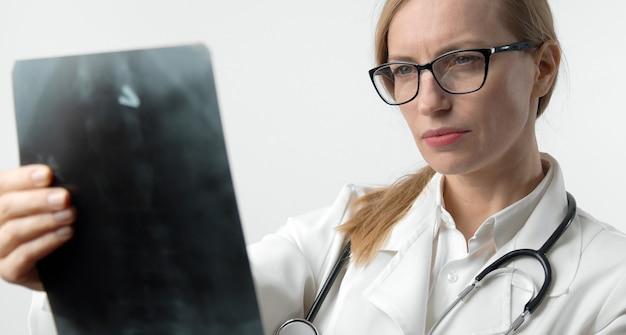 Retrato recortado de médica madura focada segurando xrayimagem olhando para os resultados da radiografia