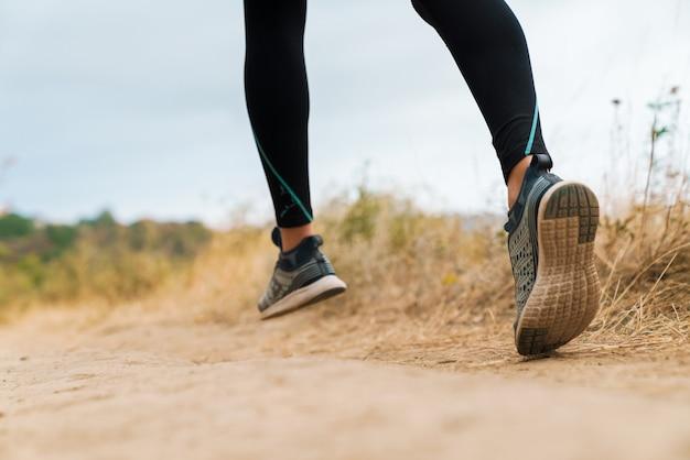 Retrato recortado de mulher atlética em roupas esportivas, correndo enquanto malharia na praia