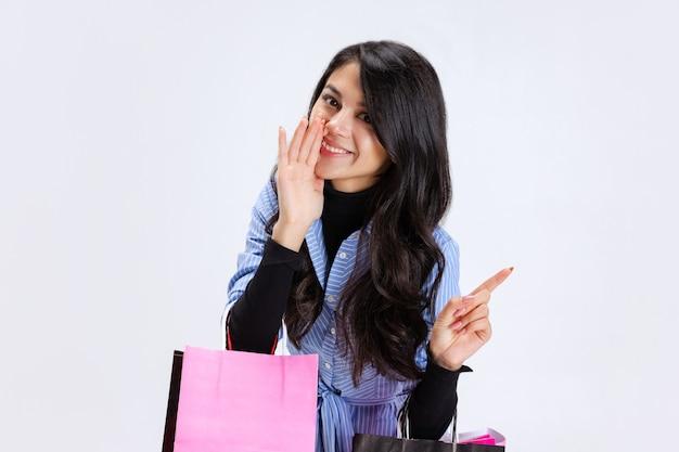 Retrato recortado de mulher elegante com sacolas de compras falando isolado no fundo branco