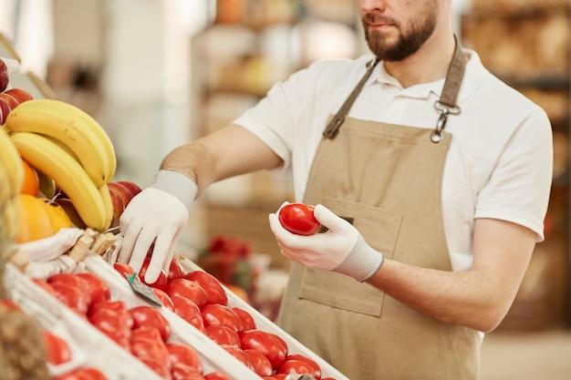 Retrato recortado de um homem barbudo segurando tomates orgânicos frescos enquanto vende produtos locais em uma barraca de frutas e vegetais no mercado de produtores