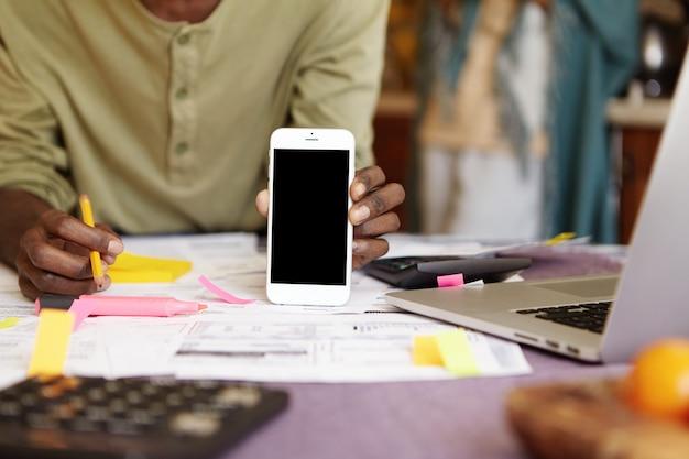 Retrato recortado de um homem de pele escura segurando um celular com tela de cópia em preto