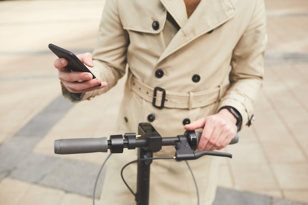 Retrato recortado de um jovem irreconhecível vestindo sobretudo segurando um smartphone enquanto dirigia uma scooter elétrica em um ambiente urbano, copie o espaço