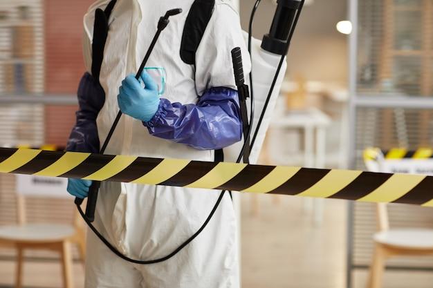 Retrato recortado de um trabalhador de desinfecção irreconhecível, usando equipamento de proteção completo, em pé atrás da linha de perigo enquanto higieniza o escritório, copie o espaço